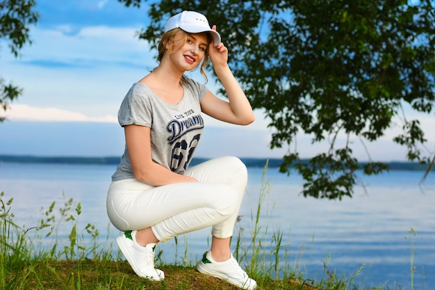 Ragazza romantica in abiti sportivi con un berretto alla luce del sole