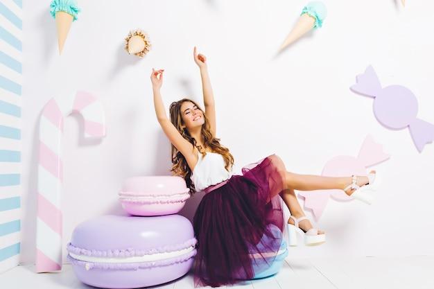 Ragazza romantica in scarpe col tacco bianche alla moda divertendosi alla sua festa di compleanno, seduto sul biscotto giocattolo in attesa di amici. splendida giovane donna in gonna viola lussureggiante rilassante nella sua camera decorata in modo carino.