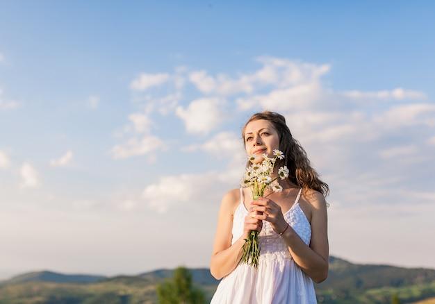 Ragazza romantica smilling dei giovani con il mazzo dei wildflowers sui precedenti di cielo blu