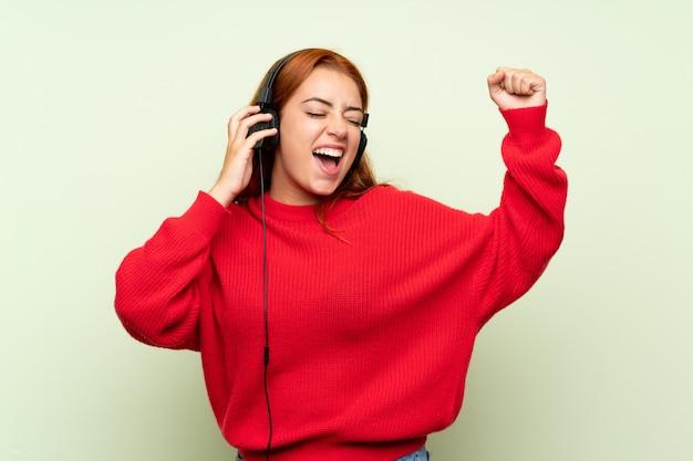 Ragazza rossa adolescente con maglione ascoltando musica con le cuffie