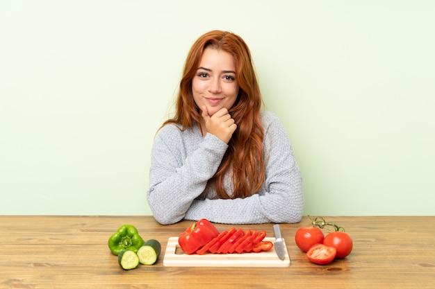 Ragazza rossa adolescente con verdure in una risata del tavolo