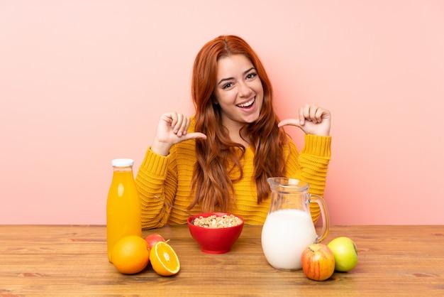 Ragazza rossa adolescente fare colazione in un tavolo orgoglioso e soddisfatto di sé