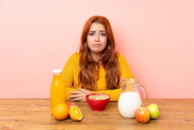 Ragazza rossa adolescente fare colazione in un tavolo triste