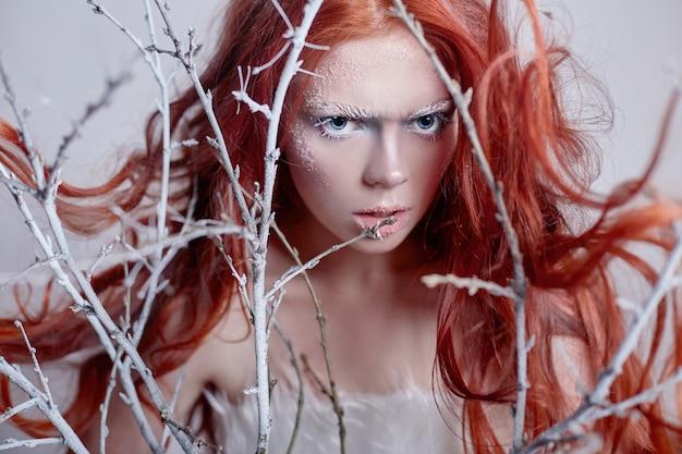 Ragazza rossa con la faccia di capelli lunghi coperti di neve