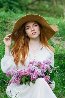 Ragazza rossa con un mazzo di lillà in un giardino di primavera