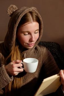 Ragazza rossa dello zenzero in divertente libro di lettura con cappuccio, bere caffè, sdraiato sul divano e sorridente