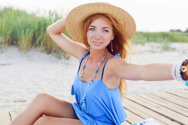 Ragazza rossa felice che fa autoritratto sulla spiaggia. tenendo il cappello di paglia. braccialetti e collana alla moda giurando.