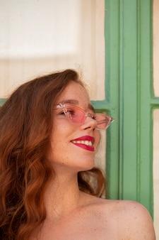 Ragazza rossa in posa con gli occhiali da sole