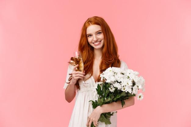 Ragazza rossa romantica con bellissimo bouquet floreale in abito bianco, tenendo champagne di vetro e sorridente