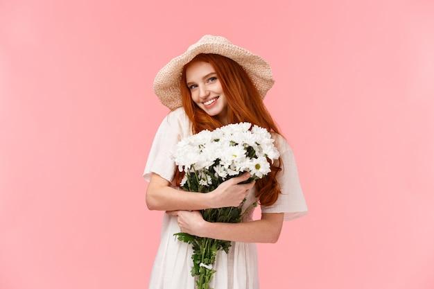 Ragazza rossa romantica con bellissimo bouquet floreale in abito bianco