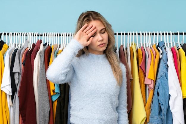 Ragazza russa dell'adolescente che compra dei vestiti isolati sull'azzurro con l'espressione stanca e malata