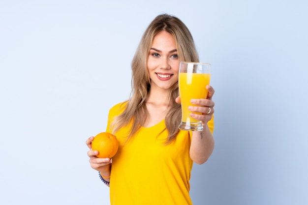 Ragazza russa dell'adolescente che tiene un'arancia sulla parete blu