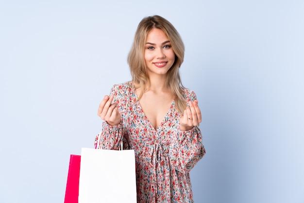 Ragazza russa dell'adolescente con il sacchetto della spesa sulla parete blu che fa gesto dei soldi
