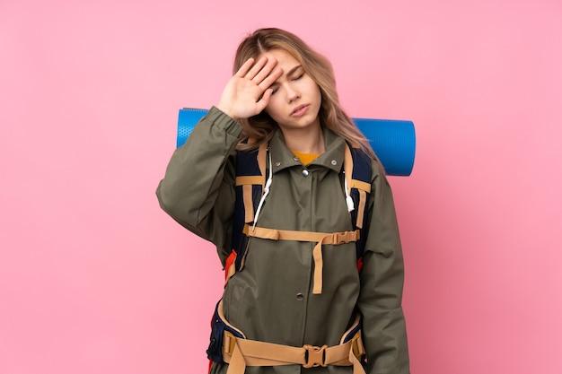 Ragazza russa dell'alpinista dell'adolescente con un grande zaino isolato sul colore rosa con l'espressione stanca e malata