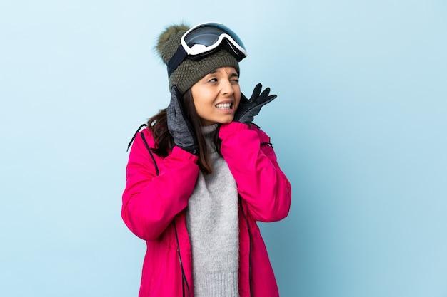 Ragazza sciatore con occhiali da snowboard frustrato e che copre le orecchie
