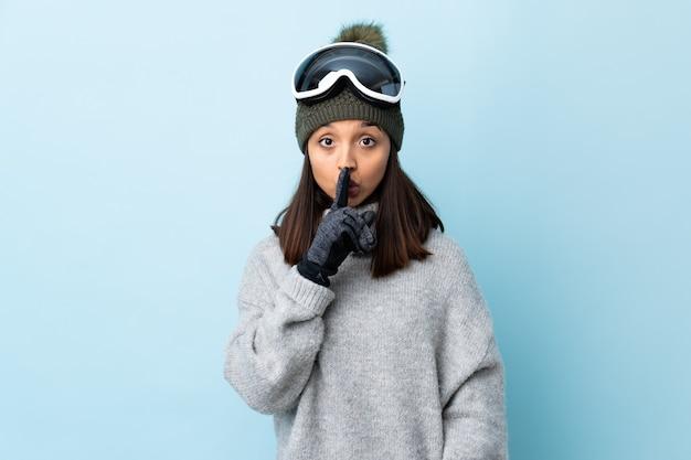 Ragazza sciatore da corsa con occhiali da snowboard che mostra un segno di silenzio