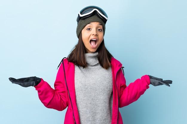 Ragazza sciatore da corsa con occhiali da snowboard con espressione facciale scioccata