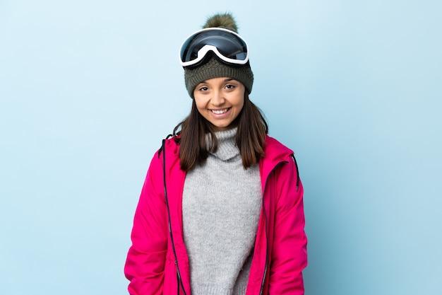 Ragazza sciatore di corsa con gli occhiali da snowboard ridendo