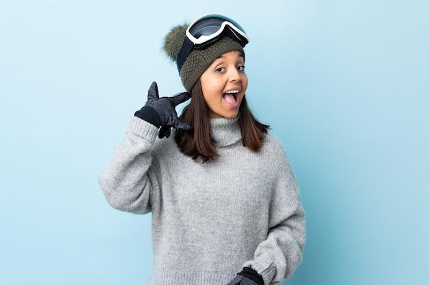 Ragazza sciatore di corsa con occhiali da snowboard che fa il gesto del telefono