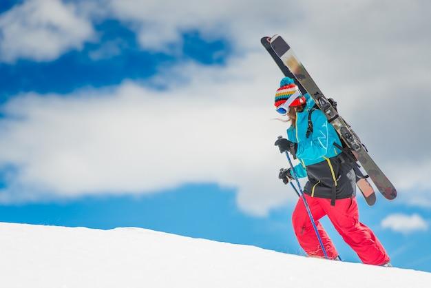 Ragazza sciatrice freeride, scala la montagna prima della discesa