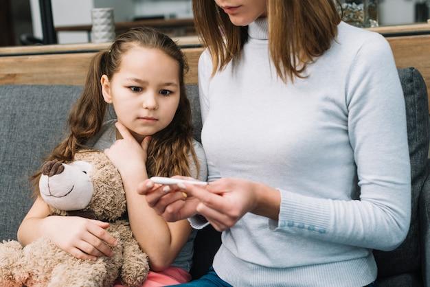 Ragazza scioccata che soffre di raffreddore e febbre guardando il termometro di sua madre