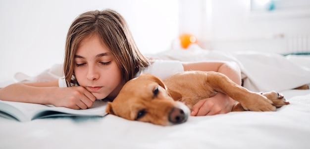 Ragazza sdraiata nel letto con il suo cane e il libro di lettura