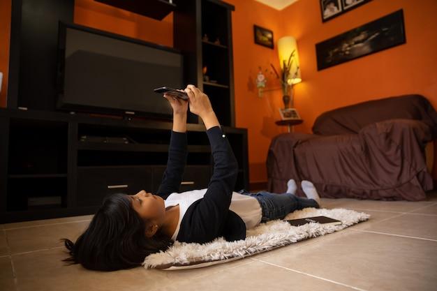 Ragazza sdraiata su una stuoia con il cellulare tra le braccia distese a casa
