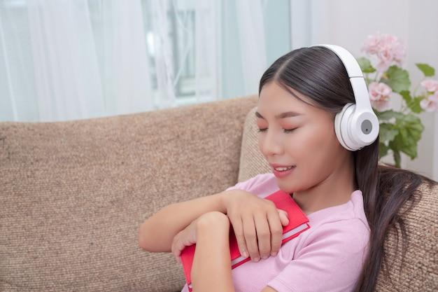 Ragazza sdraiata sul divano ascoltando musica e leggendo libri.