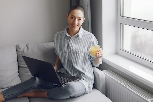 Ragazza seduta a casa e utilizzare il computer portatile