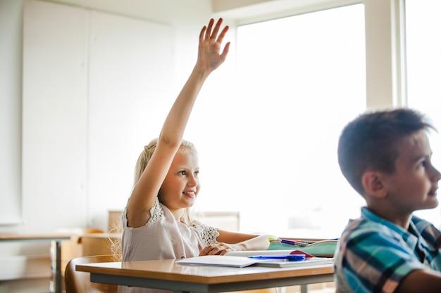 Ragazza seduta a mano alzando la mano
