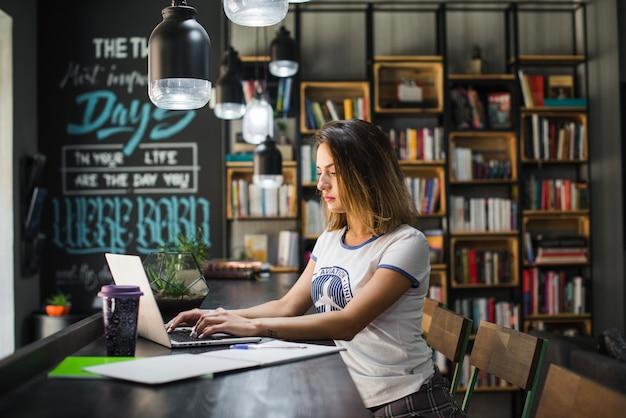 Ragazza seduta a tavola lavorando al computer portatile