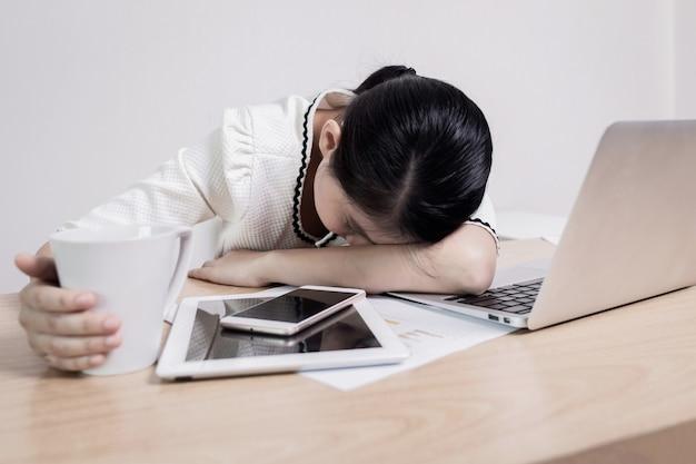 Ragazza seduta con la testa sulla scrivania
