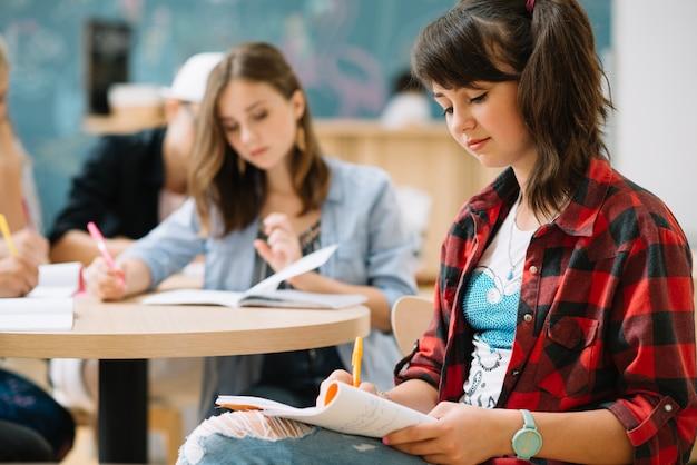 Ragazza seduta e studiando