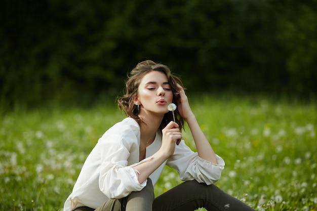 Ragazza seduta in un campo sull'erba primaverile con fiori di tarassaco