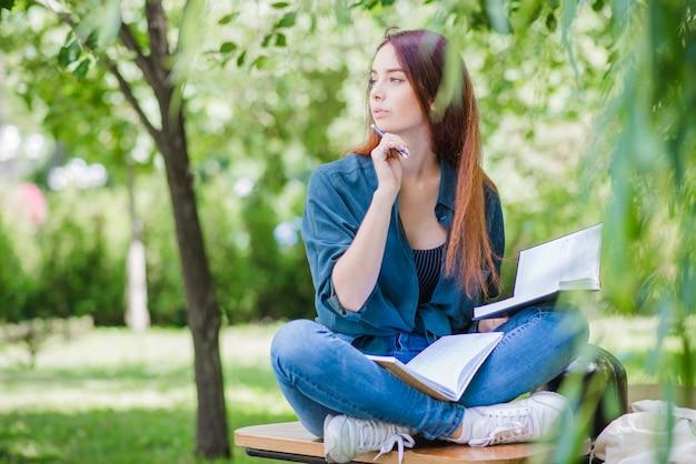 Ragazza seduta nel parco studiando guardando lontano