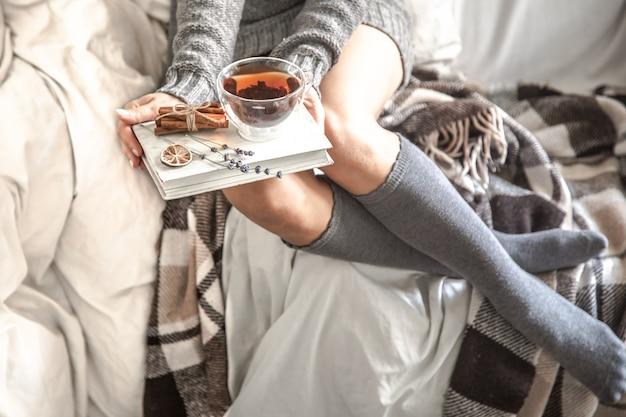 Ragazza seduta su un accogliente letto caldo con tè e un libro, il concetto di comfort e hipster