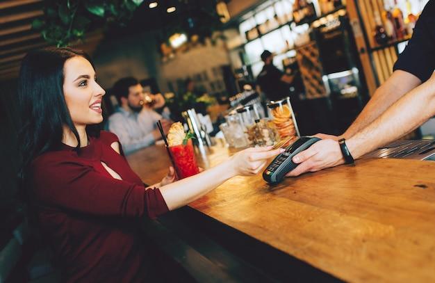 Ragazza seduta vicino al barista e pagando il suo ordine