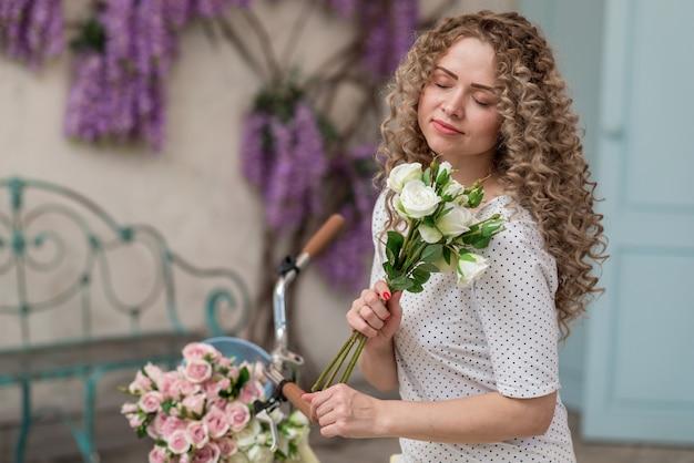 Ragazza sensuale con gli occhi chiusi che tiene un mazzo di fiori all'aperto. - immagine