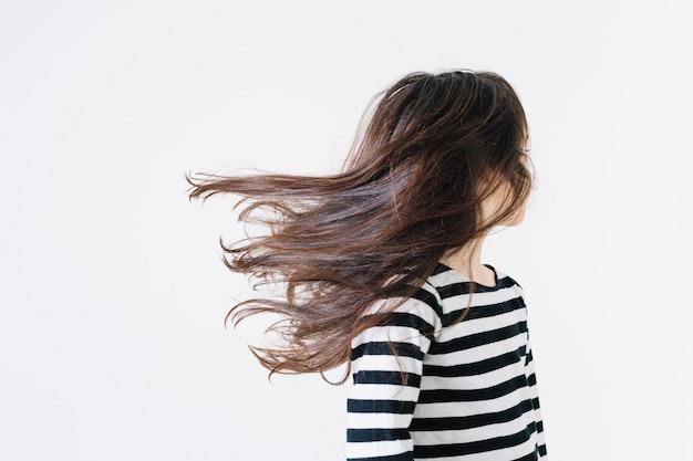 Ragazza senza volto che agita i capelli