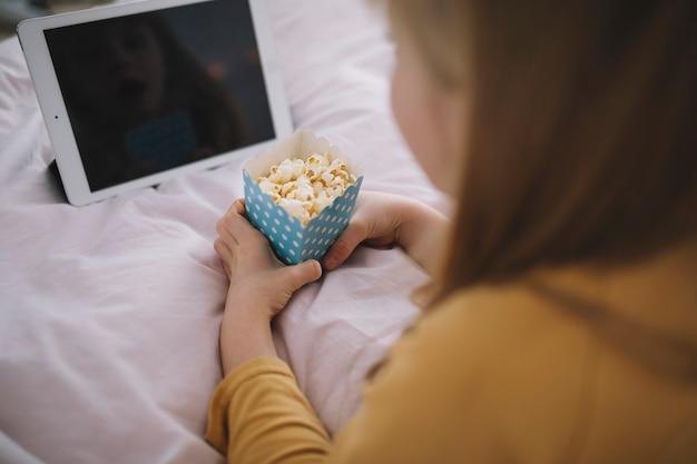 Ragazza senza volto che guarda film sul tablet