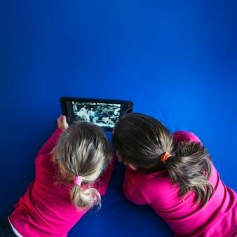 Ragazza senza volto che guarda video sul tablet