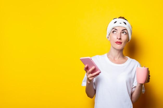 Ragazza seria in una benda guarda al lato con un telefono e una tazza di caffè su uno sfondo giallo