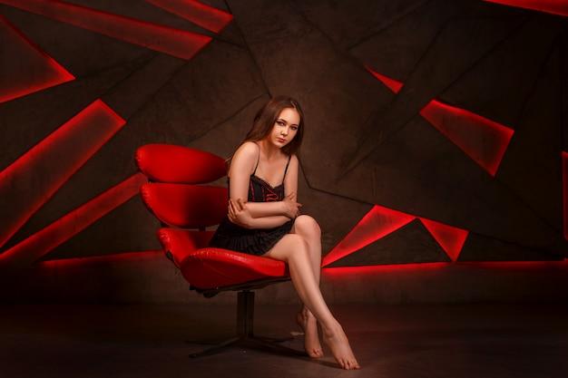 Ragazza sessuale con i capelli scuri, seduta su una poltrona rossa