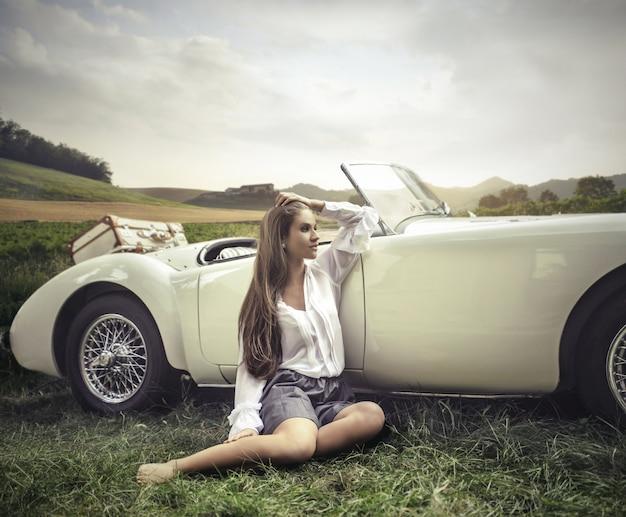 Ragazza sexy accanto a un'auto sportiva