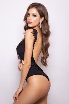 Ragazza sexy alla moda in un costume da bagno nero isolato su uno sfondo di wight