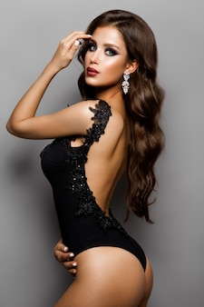 Ragazza sexy alla moda in un costume da bagno nero isolato su uno sfondo grigio