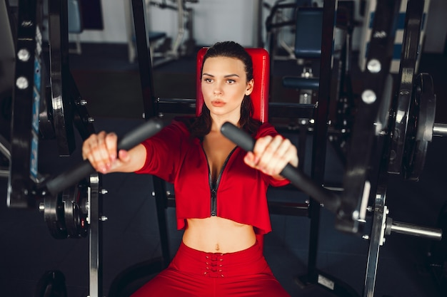 Ragazza sexy che fa le esercitazioni nei suoi muscoli pettorali in simulatore.
