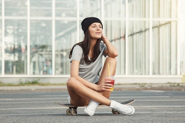 Ragazza sexy che si siede sullo skateboard