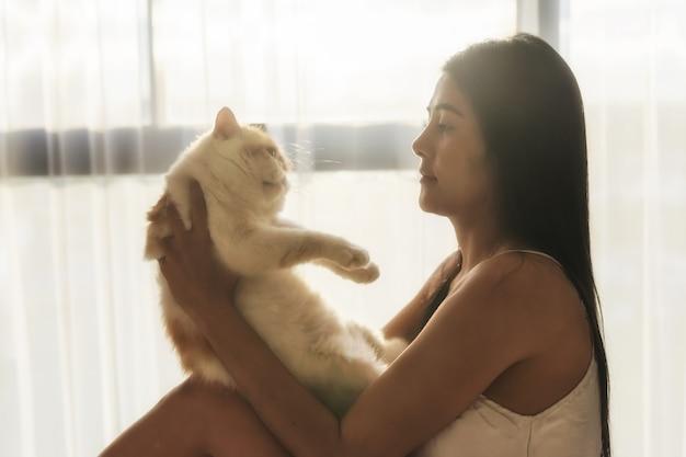 Ragazza sexy con gatto in camera da letto