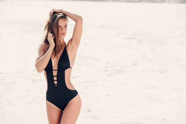 Ragazza sexy con un corpo sportivo perfetto in costume da bagno nero rilassante in spiaggia.